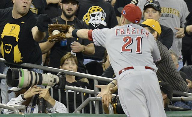 Cincinnati Reds third baseman Todd Frazier (21) reaches into the photographers' pit to catch a fly ball by Pittsburgh Pirates' Justin Morneau in the third inning of the NL wild-card playoff baseball game Tuesday, Oct. 1, 2013, in Pittsburgh. (AP Photo/Don Wright)