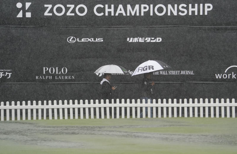 People hold umbrellas in the rain as they walk past near the practice area after the second round of the Zozo Championship PGA Tour is postponed due to heavy rain at the Accordia Golf Narashino country club in Inzai, east of Tokyo, Japan, Friday, Oct. 25, 2019. (AP Photo/Lee Jin-man)