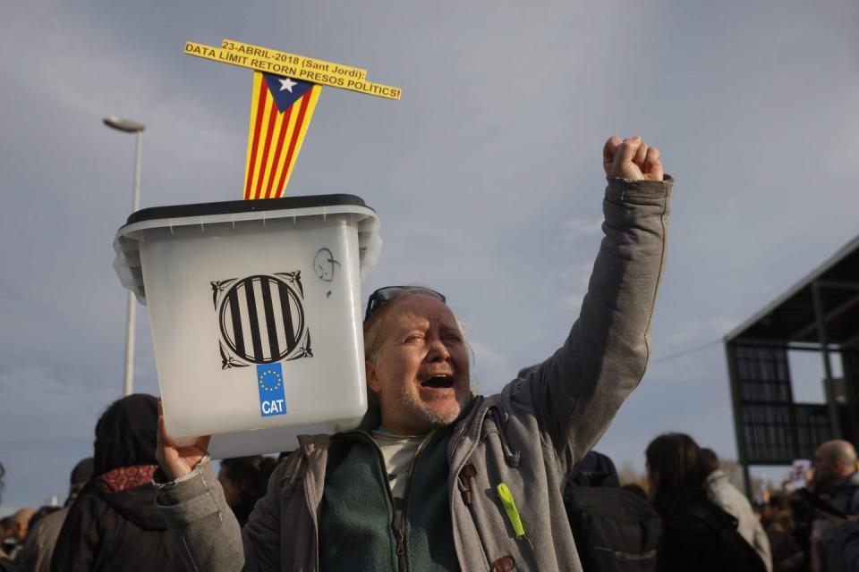A man holds up a ballot box during a protest.