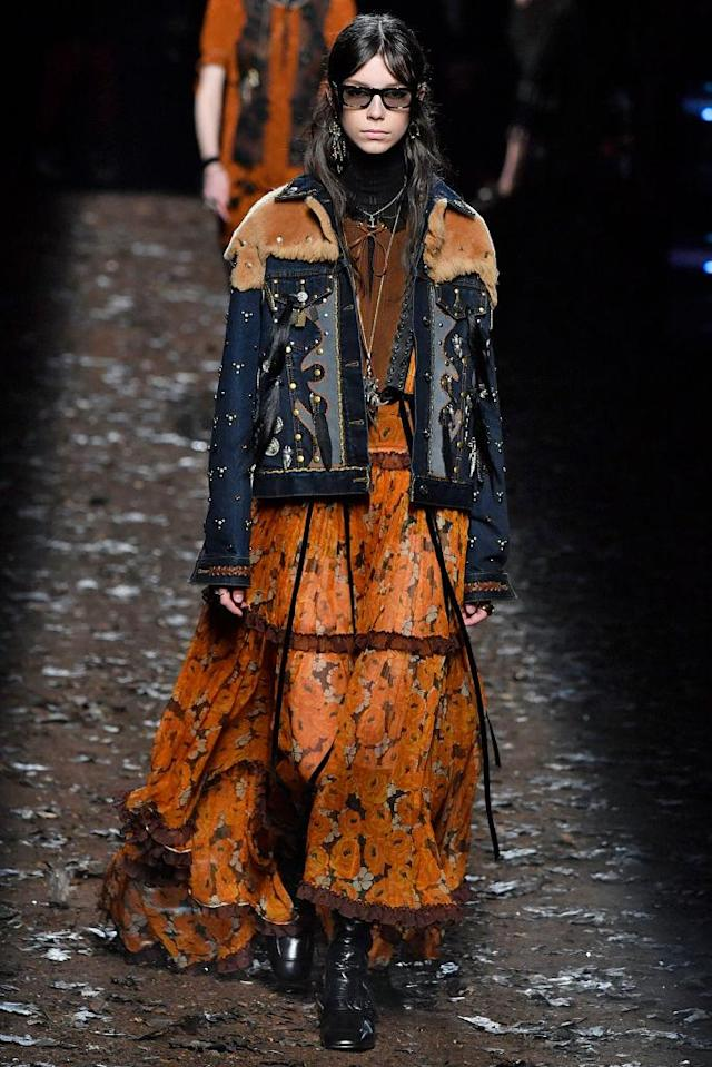 <p>Model wears a denim jacket with studs and shearling panels over an orange rose-print tiered dress at the Coach Fall 2018 show. (Photo: Getty) </p>