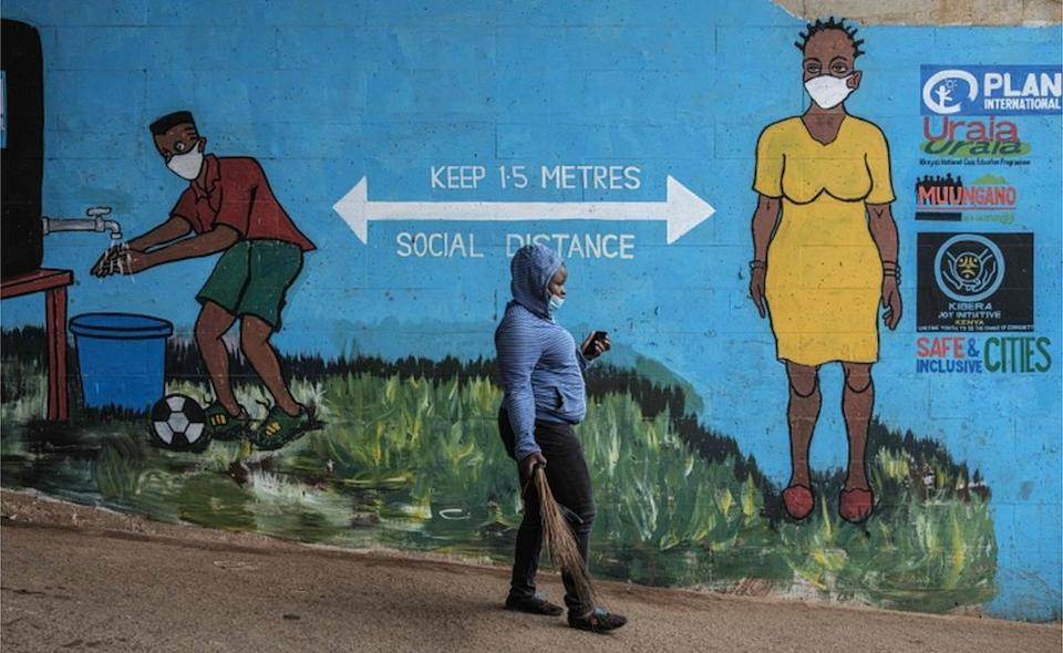 On Wednesday a woman walks past a mural reminding residents of Nairobi to maintain social distancing.