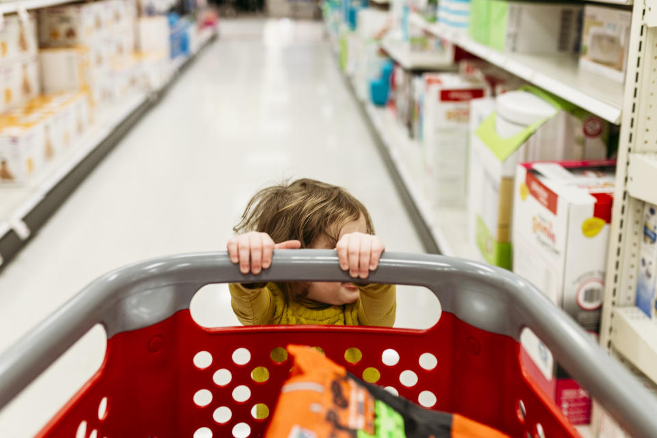 Child holding on to a trolley in a supermarket
