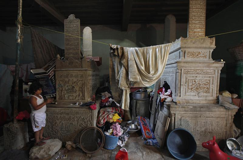 In this photo taken in Monday, May 21, 2012, a boy plays next to tombs in a room where his family lives in a necropolis called the City of the Dead, in Cairo, Egypt. The City of the Dead is a 4 mile (6.4 kilometer) long necropolis where thousands of Egyptians are forced to live and work alongside graves due to the scarcity of housing in the capital. (AP Photo/Khalil Hamra)