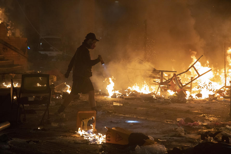 A protester walks past burning debris as police storm part of the Hong Kong Polytechnic University campus during the early morning hours in Hong Kong, Monday, Nov. 18, 2019. Police breached the university campus held by protesters early Monday after an all-night siege that included firing repeated barrages of tear gas and water cannons. (AP Photo/Ng Han Guan)