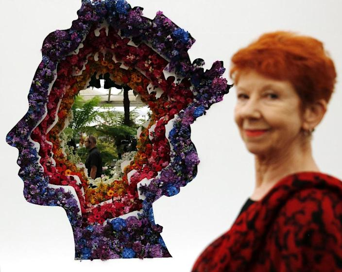 British actress Carol Boyd stands beside New Covent Garden Flower Market's display stand, which features an image of Britain's Queen Elizabeth II, at the 2016 Chelsea Flower Show in London, on May 23, 2016 (AFP Photo/Adrian Dennis)