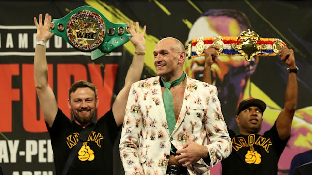 "Trainers Andy Lee (L) and Javan ""SugarHill"" Steward (R) hold up the belts as WBC/lineal heavyweight champion Tyson Fury arrives at his news conference Saturday after stopping Deontay Wilder. (Bradley Collyer/Getty Images)"