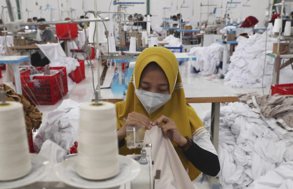 Workers wearing face masks to curb the spread of the coronavirus outbreak operate sewing machines at a factory that makes Muslim women's prayer robes in Depok, Indonesia, Wednesday, April 7, 2021. (AP Photo/Tatan Syuflana)
