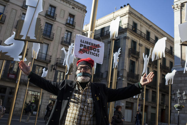 "A man stands next to a banner reading in Catalan,""Freedom for Political Prisoners,"" in support of Catalan politicians who have been jailed on charges of sedition, in Barcelona Dec. 19. (Photo: Jose Colon/MeMo for Yahoo News)"