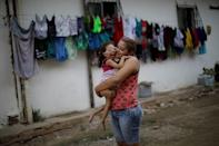 """Gabriela Alves de Azevedo, 22, holds her two-year-old daughter Ana Sophia, who was born with microcephaly, at their house in Olinda, Brazil, August 7, 2018. Gabriela had planned to finish high school and study physical therapy. Now, she spends her days caring for her child. Her husband left shortly after Ana Sophia's birth. He could not accept their child's condition, Gabriela says, and does not pay child support. """"I went into depression and my family helped me,"""" she said. """"If it was not for them, I would have gone crazy."""" REUTERS/Ueslei Marcelino/Files"""