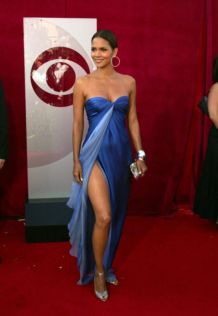 Halle Berry at the 2005 emmys wearing a blue gown with a high slit on the red carpet