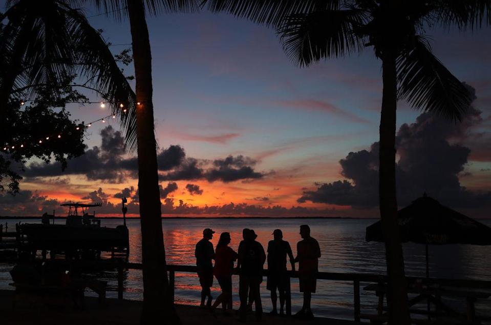 """People enjoy the sunset over the water in the Gulf of Mexico during the seasonal king tides on October 27, 2019 in Key Largo, Florida.<span class=""""copyright"""">Joe Raedle—Getty Images</span>"""