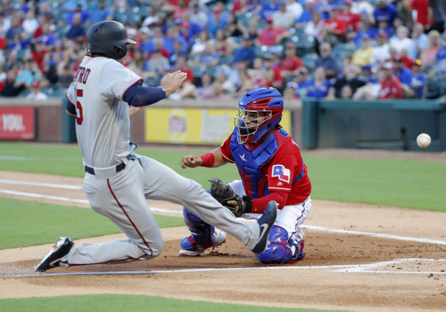 Minnesota Twins' Jason Castro scores on a fielders choice by Max Kepler as Texas Rangers catcher Jose Trevino is unable to field the throw to the bag in the second inning of a baseball game in Arlington, Texas, Thursday, Aug. 15, 2019. Jake Cave also scored on the play with a throwing error charged to the Rangers' Elvis Andrus. (AP Photo/Tony Gutierrez)
