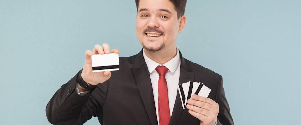 Happiness business man holding many cards. One bank card will replace all your cards. Indoor, studio shot, isolated on light blue or gray background