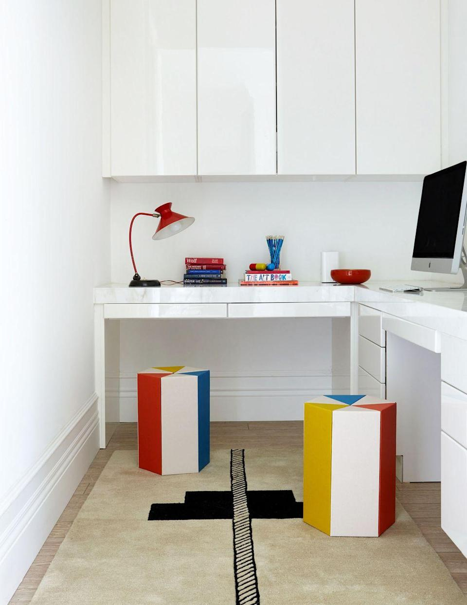 """<p>If you have a small makeshift home office in the corner of a larger room or you're converting a walk-in closet, opt for glossy white lacquered cabinets and furniture. Similar to the maximizing effect of a mirror, the reflective surfaces will give the illusion of a larger, more open space. Designer <a href=""""http://www.rajirm.com/"""" rel=""""nofollow noopener"""" target=""""_blank"""" data-ylk=""""slk:Raji Radhakrishnan"""" class=""""link rapid-noclick-resp"""">Raji Radhakrishnan</a> gave <a href=""""https://www.housebeautiful.com/design-inspiration/house-tours/a30696950/raji-rm-piet-boon-virginia/"""" rel=""""nofollow noopener"""" target=""""_blank"""" data-ylk=""""slk:this"""" class=""""link rapid-noclick-resp"""">this</a> home office some pops of fun and vibrancy with primary colored stools and a graphic rug. </p>"""