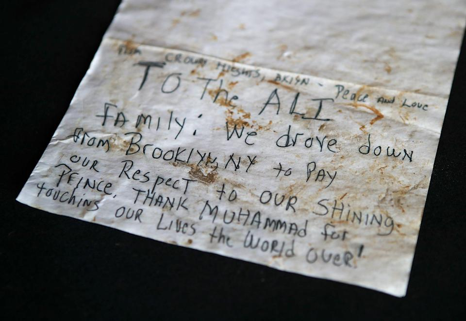 """Dozens of handwritten cards and letters have appeared at Muhammad Ali's grave since he died in 2016. This card says """"To the Ali family: We drove down from Booklyn NY to pay our respects to our shining prince. Thank Muhammad for touching our lives the world over!"""""""