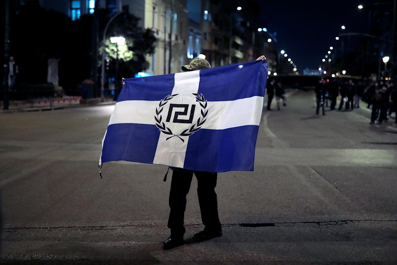 A supporter of Greece's far-right Golden Dawn party waves an old Greek national flag with the party's emblem during a protest against Turkey in Athens, Greece, March 5, 2018. REUTERS/Alkis Konstantinidis