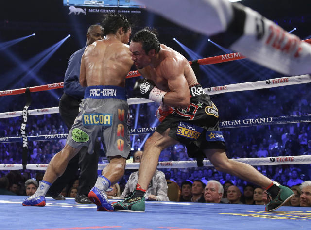 Juan Manuel Marquez, from Mexico, right, knocks out Manny Pacquiao, from the Philippines, in the sixth round of their WBO world welterweight fight Saturday, Dec. 8, 2012, in Las Vegas. Referee Kenny Bayless looks on at left rear. (AP Photo/Julie Jacobson)