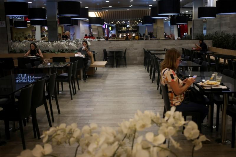 People eat in a food court mall at lunch time amid the coronavirus disease (COVID-19) outbreak in Sao Paulo