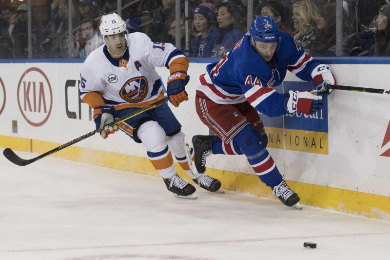 FILE - In this Jan. 10, 2019, file photo, New York Rangers defenseman Neal Pionk (44) and New York Islanders right wing Cal Clutterbuck (15) chase the puck during the first period of an NHL hockey game in New York. The Rangers have acquired defenseman Jacob Trouba from the Winnipeg Jets for Pionk and the 20th overall pick in the draft. The teams announced the trade Monday, June 17, 2019. (AP Photo/Mary Altaffer, File)