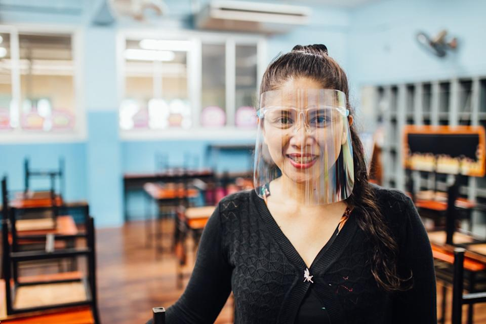female teacher wearing face shield smiling while standing in classroom