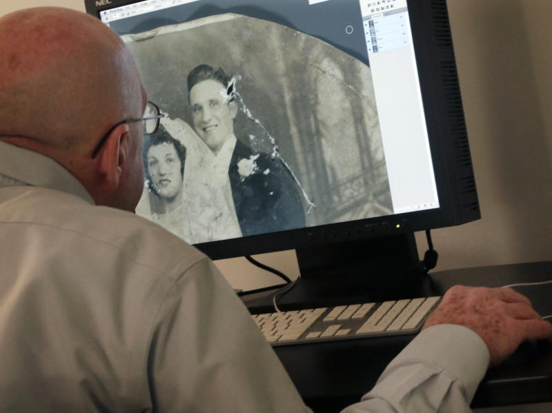 In this Saturday, Feb. 2, 2013 image, photo restorer Dennis McKeever uses Photoshop to retouch a damaged photo belonging to Florence Catania, of Deer Park, N.Y., during the restoration project of Operation Photo Rescue-Hurricane Sandy, at New York's School of Visual Arts. Of all the pictures of Superstorm Sandy's destruction, some of the most lingering are the warped, stained ones that sat on the walls and shelves of flooded homes. The Sandy project promises to be one of Operation Photo Rescue's most expert and ambitious efforts yet. (AP Photo/Richard Drew)
