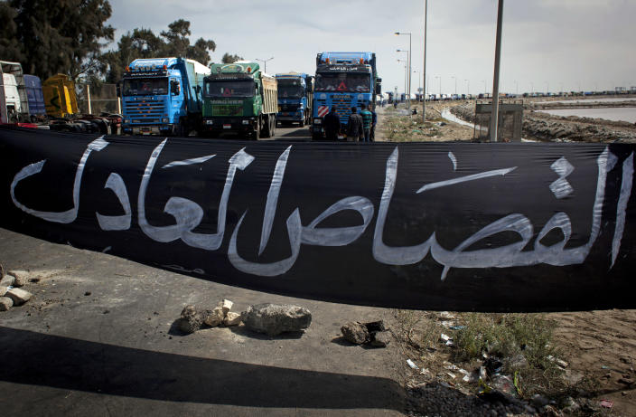"""FILE - In this Friday, Feb. 22, 2013 file photo, Egyptian protesters, unseen, block a road preventing loaded trucks from leaving the port with a banner in Arabic that reads, """"fair retribution,"""" during a general strike, in Port Said, Egypt. For nearly two weeks, protesters and strikers have shut down much of Egypt's Mediterranean city of Port Said, filling the streets with one angry rally after another. Opponents of Egypt's Islamist president are looking to Port Said as a model for stepping up their campaign against him with a possible wave of civil disobedience in other parts of the country. (AP Photo/Nasser Nasser, File)"""