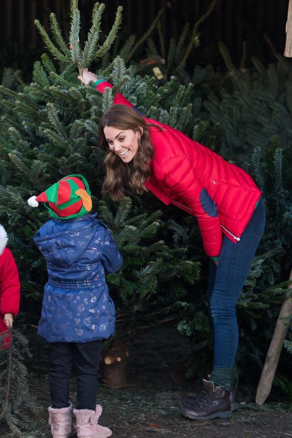<p>The duchess helps a child pick out a Christmas tree at a Family Action charity event.</p>