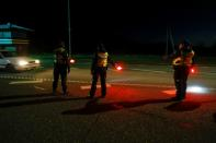 Estonian police and border guard officers show the car driver where to go at border crossing point in Ikla