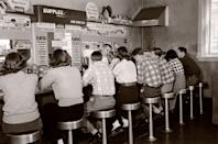 <p>A row of customers line counter at this busy 1950s establishment. </p>