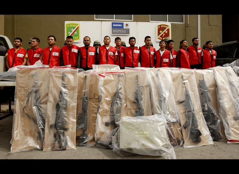 Fourteen alleged members of 'Los Zetas' drug cartel and seized weapons are presented to the press in Monterrey, Nuevo Leon state, Mexico on February 15, 2012. More than 40,000 people have been killed in rising drug-related violence in Mexico since December 2006, when President Felipe Calderon deployed soldiers and federal police to take on organized crime. (Julio Cesar Aguilar/AFP/Getty Images)