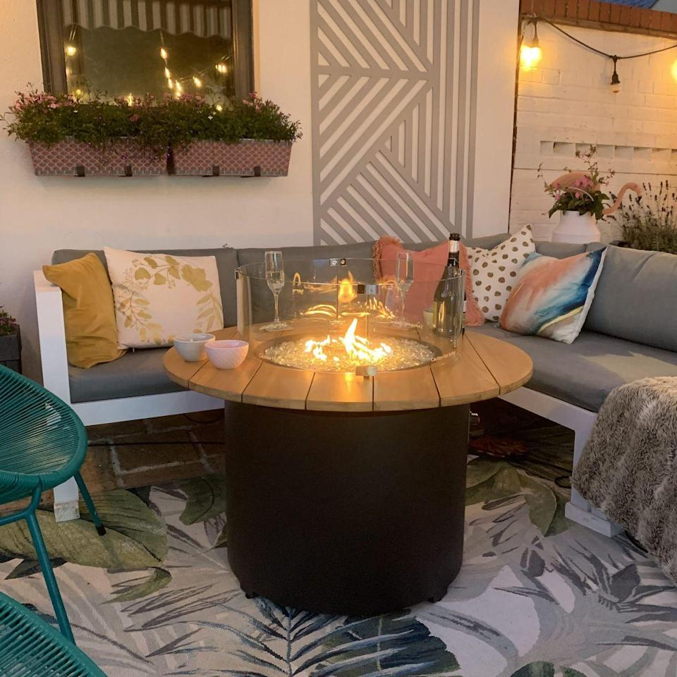 """<p>Come evening, it's the perfect spot to unwind and keep warm thanks to the compact fire pit table.</p><p><strong>READ MORE: </strong><a href=""""https://www.housebeautiful.com/uk/garden/g32185721/fire-pit/"""" rel=""""nofollow noopener"""" target=""""_blank"""" data-ylk=""""slk:Best fire pits for your patio or garden"""" class=""""link rapid-noclick-resp"""">Best fire pits for your patio or garden</a></p>"""