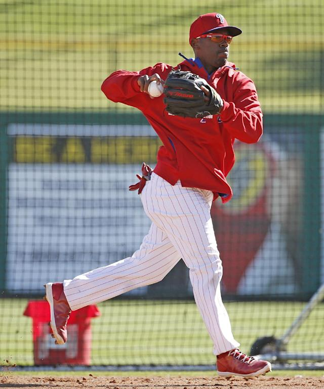 Philadelphia Phillies shortstop Jimmy Rollins throws to first while fielding balls during batting practice before a spring exhibition baseball game against the New York Yankees, in Clearwater, Fla., Thursday, March 13, 2014. Rollins was out of the starting lineup Yankees, benched for a third straight game. Rollins said he's healthy and unsure why manager Ryne Sandberg decided to bench him this week. (AP Photo/Kathy Willens, File)