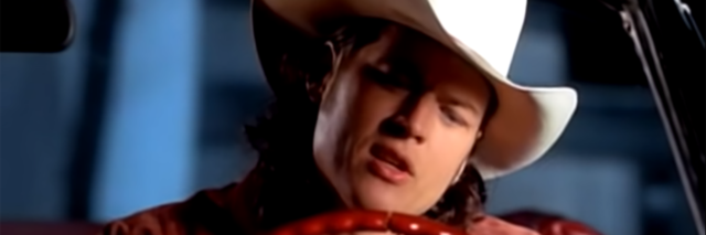 Blake Shelton wearing a cowboy hat and driving a red car.