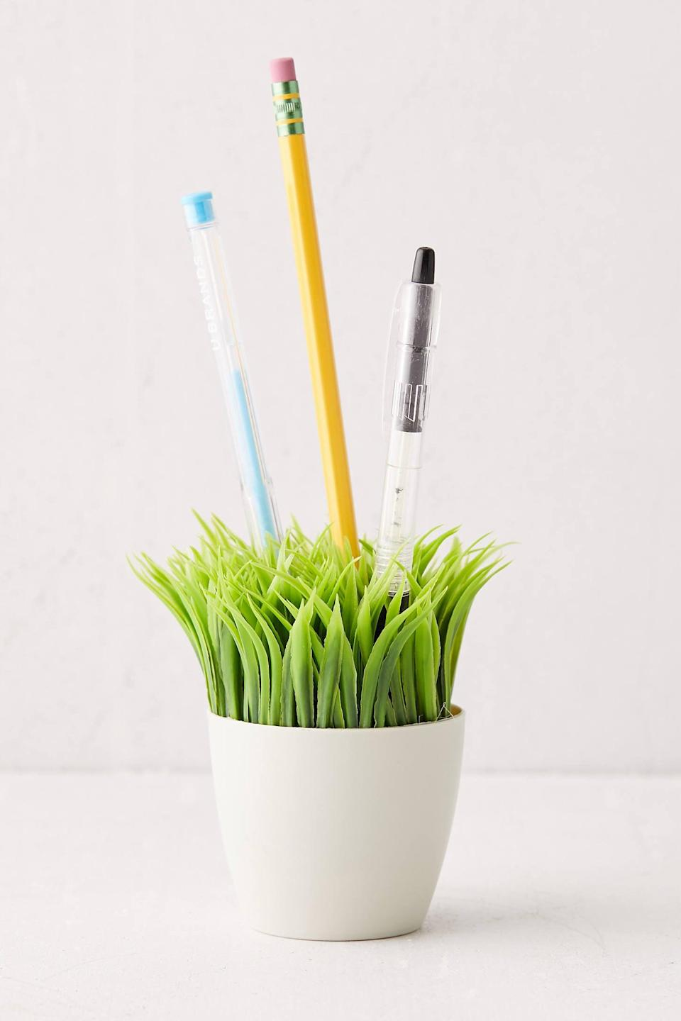 """<h2>Grass Pen Stand<br></h2><br>Attention: that random cup holding our pens is OUT and this super clever pen holder is IN. Guaranteed to make anyone constantly glued to their desk drafting stanzas smile. <br><br><em>Shop </em><a href=""""https://fave.co/31sH03T"""" rel=""""nofollow noopener"""" target=""""_blank"""" data-ylk=""""slk:Urban Outfitters"""" class=""""link rapid-noclick-resp""""><em><strong>Urban Outfitters</strong></em></a><br><br><strong>Urban Outfitters</strong> Grass Pen Stand, $, available at <a href=""""https://go.skimresources.com/?id=30283X879131&url=https%3A%2F%2Ffave.co%2F2H8AVCN"""" rel=""""nofollow noopener"""" target=""""_blank"""" data-ylk=""""slk:Urban Outfitters"""" class=""""link rapid-noclick-resp"""">Urban Outfitters</a>"""