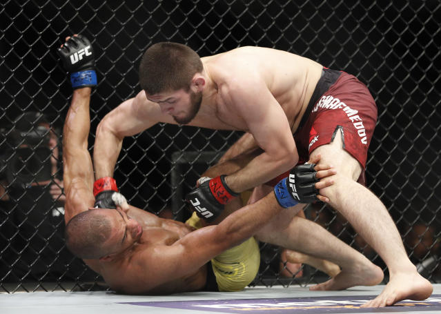 Khabib Nurmagomedov hits Edson Barboza during a lightweight mixed martial arts bout at UFC 219, Saturday, Dec. 30, 2017, in Las Vegas. (AP Photo/John Locher)