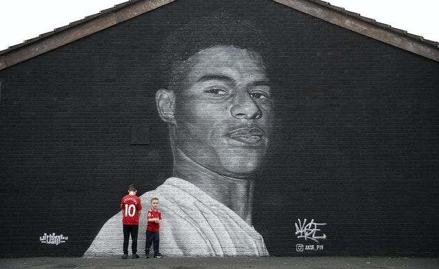 Manchester United fans pose in front of a mural of striker Marcus Rashford