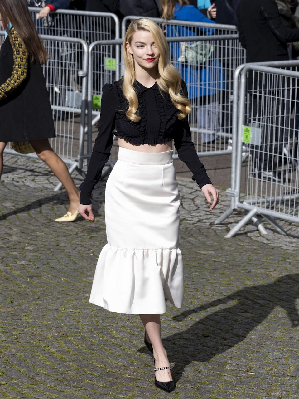 <p>Anya was spotted during Paris Fashion Week's fall 2021 season in head-to-toe Miu Miu outside of the show. She teamed a Victorian-inspired crop top with a fluted skirt and embellished patent pumps.</p>