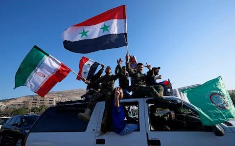 Syrian government supporters wave Syrian, Iranian and Russian flags as they chant slogans against U.S. President Trump during demonstrations following a wave of U.S., British and French military strikes - Credit: AP