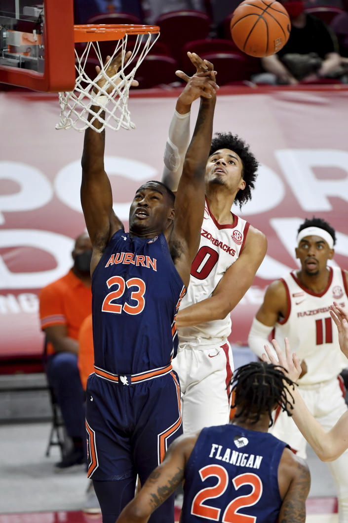 Arkansas forward Justin Smith (0) and Auburn forward Jaylin Williams (23) reach for a rebound during the first half of an NCAA college basketball game Wednesday, Jan. 20, 2021, in Fayetteville, Ark. (AP Photo/Michael Woods)