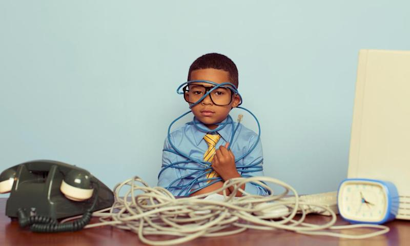 Young Boy IT Professional Smiles at Computer with Wire<br>A young IT professional sadly looks over a large pile of tangled internet cables on his desk. He is dressed in a blue shirt, tie and glasses while looking over worked and tired in front of light blue backround. Retro styling.