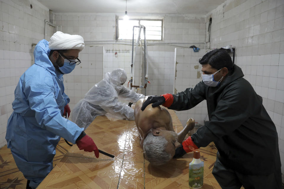 Volunteers wearing protective clothing prepare the body of a man who died from COVID-19 for a funeral at a cemetery in the outskirts of the city of Ghaemshahr, in northern Iran, Wednesday, Dec. 16, 2020. (AP Photo/Ebrahim Noroozi)