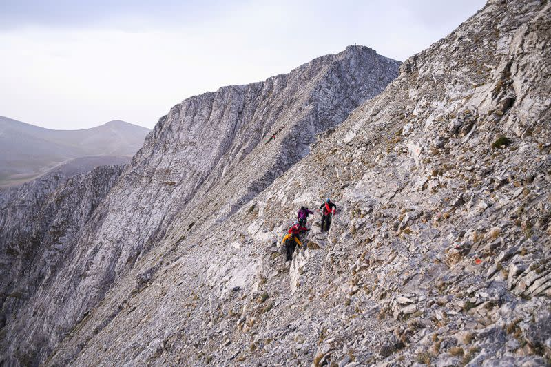 A group of climbers help Eleftheria Tosiou in her ascent to the peak of Mount Olympus