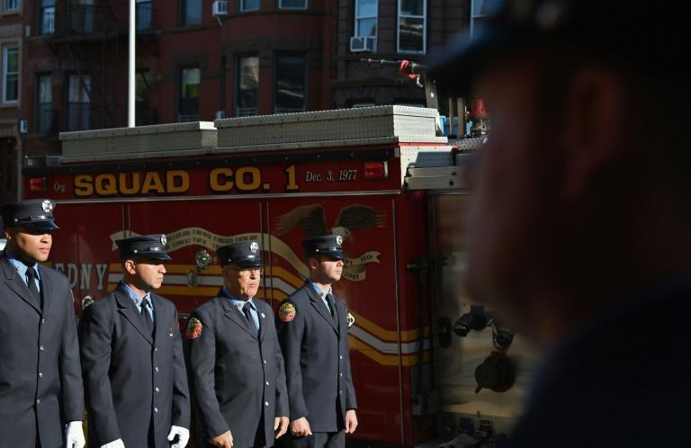 Brooklyn firefighters line up outside their station for a memorial ceremony on September 11, 2021 (AFP/ANGELA WEISS)