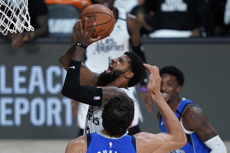 Los Angeles Clippers' Paul George, center, drives to the basket against the Dallas Mavericks during the second half of an NBA basketball first round playoff game Tuesday, Aug. 25, 2020, in Lake Buena Vista, Fla. (AP Photo/Ashley Landis, Pool)
