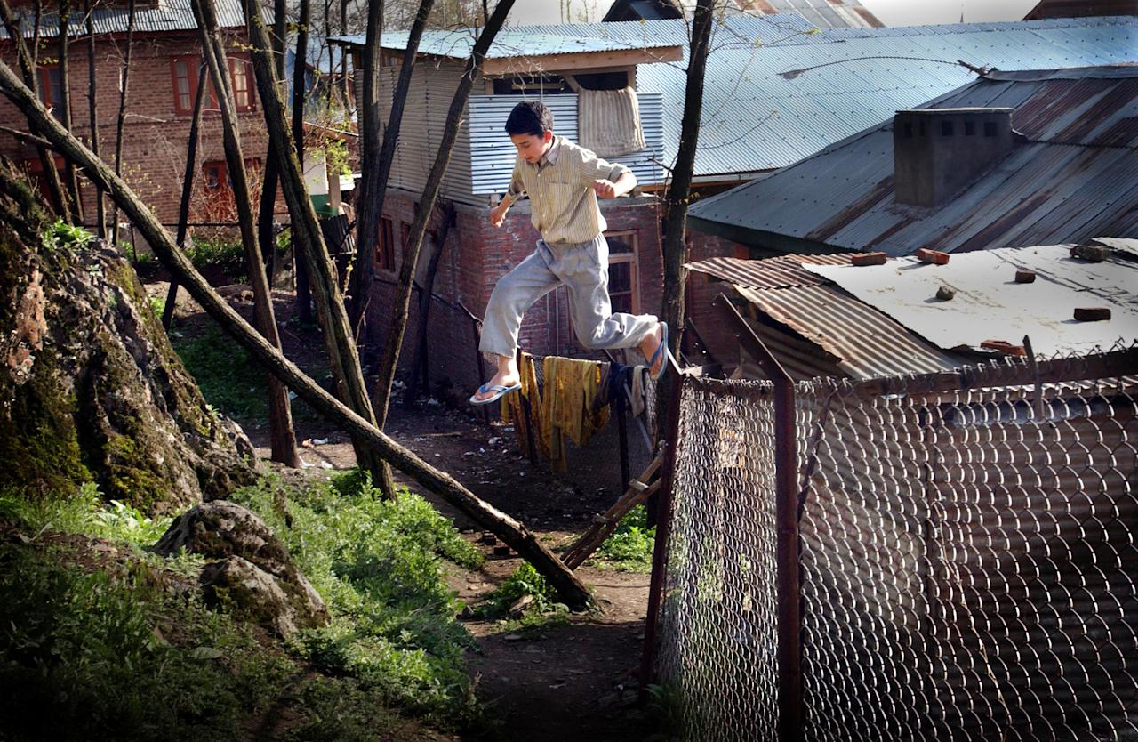403249 08: A Kashmiri child jumps over a fence to play a game of cricket with his friends living in an orphanage April 2, 2002 in Srinagar, the summer capital of the Indian held state of Jammu and Kashmir. About one third of the children have been orphaned because of the fighting between militants and Indian security forces in Kashmir. Nearly a dozen militant groups are fighting New Delhi's rule. India accuses Pakistan of arming and training Islamic militants. Pakistan denies the charge and says it only offers moral and diplomatic support to Kashmiri separatists. (Photo by Ami Vitale/Getty images)