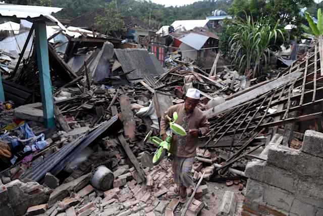 <p>A man carries a small bicycle through the ruins of houses damaged by an earthquake in West Lombok, Indonesia, Aug. 6, 2018. (Photo: Antara Foto/Zabur Karuru via Reuters) </p>