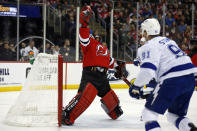 New Jersey Devils goaltender Louis Domingue, left, makes a save in front of Tampa Bay Lightning center Steven Stamkos (91) during the first period of an NHL hockey game Sunday, Jan. 12, 2020, in Newark, N.J. (AP Photo/Adam Hunger)