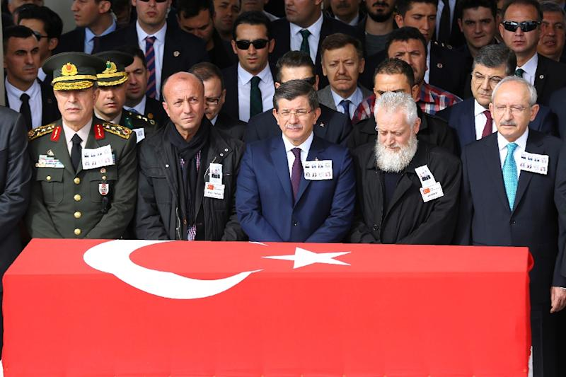 Turkish Prime Minister Ahmet Davutoglu (C) stands behind the flag-draped coffin of a car bombing victims during a funeral ceremony at Kocatepe Mosque in Ankara on February 19, 2016 (AFP Photo/Adem Altan)