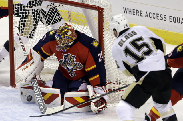 Florida Panthers goalie Jacob Markstrom (25) blocks a shot by Pittsburgh Penguins' Tanner Glass (15) in the first period of an NHL hockey game on Friday, Oct. 11, 2013, in Sunrise, Fla. (AP Photo/Alan Diaz)