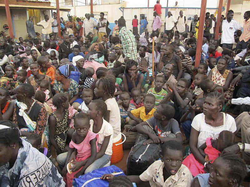 In this image released by the United Nations Mission Juba, civilians sit after arriving at the compound of the United Nations Mission in the Republic of South Sudan (UNMISS), adjacent to Juba International Airport, to take refuge Wednesday, Dec. 18 , 2013, in Juba, South Sudan. A South Sudanese army official said clashes among military factions have spread to the rural state of Jonglei in escalating violence that the government blames on forces loyal to a former deputy president. (AP Photo/UNMISS, Rolla Hinedi)
